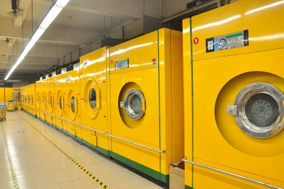 Large industrial washing machines lined up in a row.